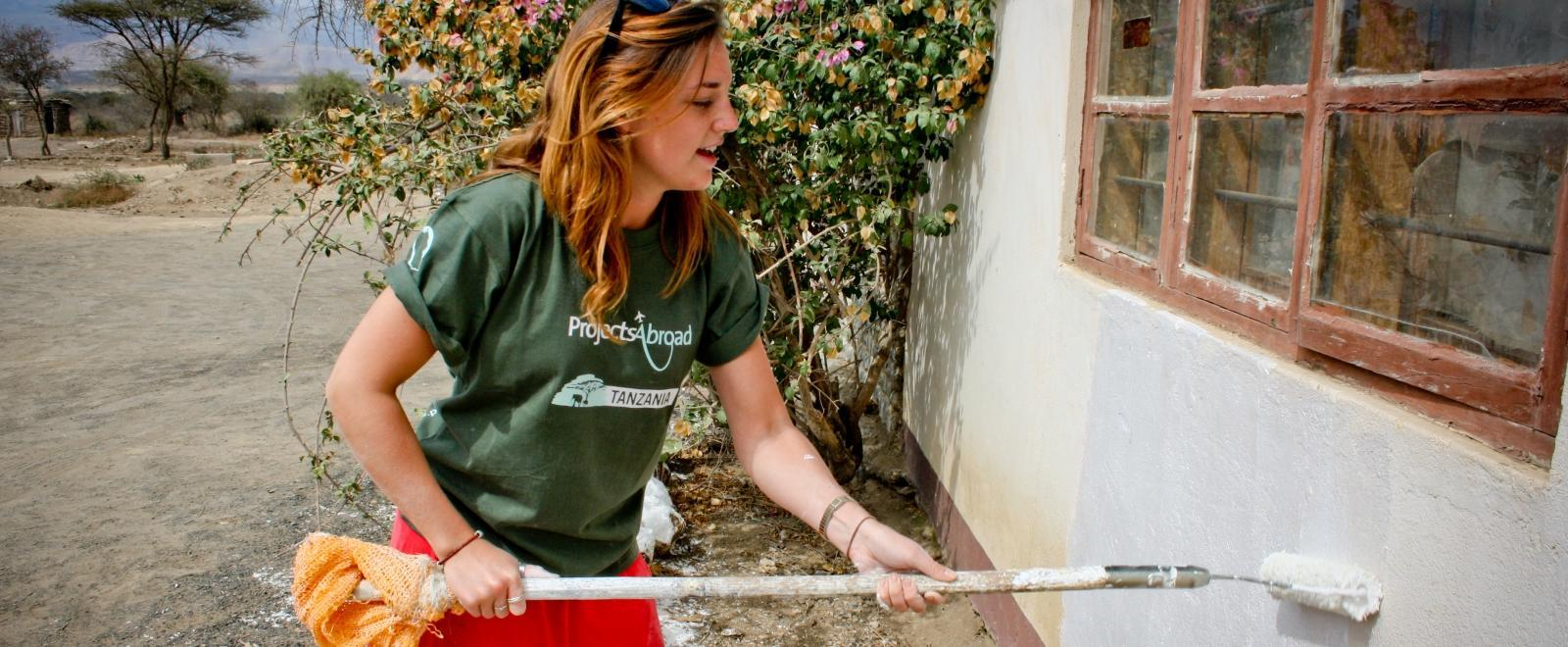 A student doing building volunteer work in Africa helps paint a newly-constructed school in Tanzania.